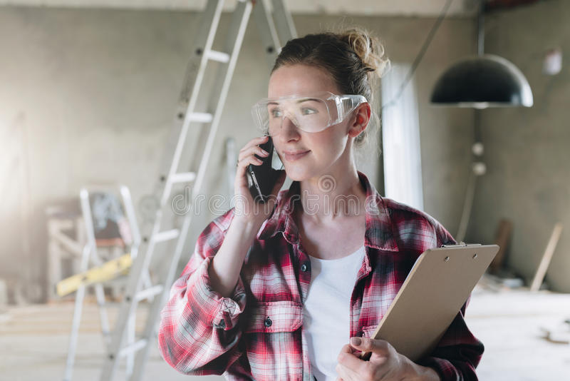 Portrait of businesswoman engineer, architect, designer.Girl standing,talking on cell phone and holding clipboard. royalty free stock photography