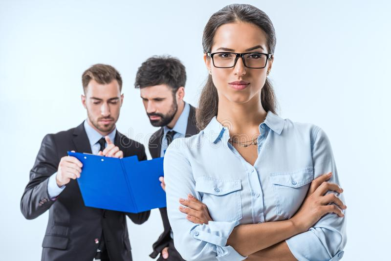 portrait of businesswoman in eyeglasses with arms crossed looking at camera while colleagues discussing work stock image
