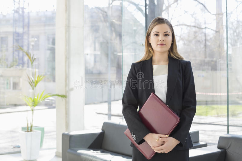 Portrait of businesswoman holding file while standing at office lobby royalty free stock photos