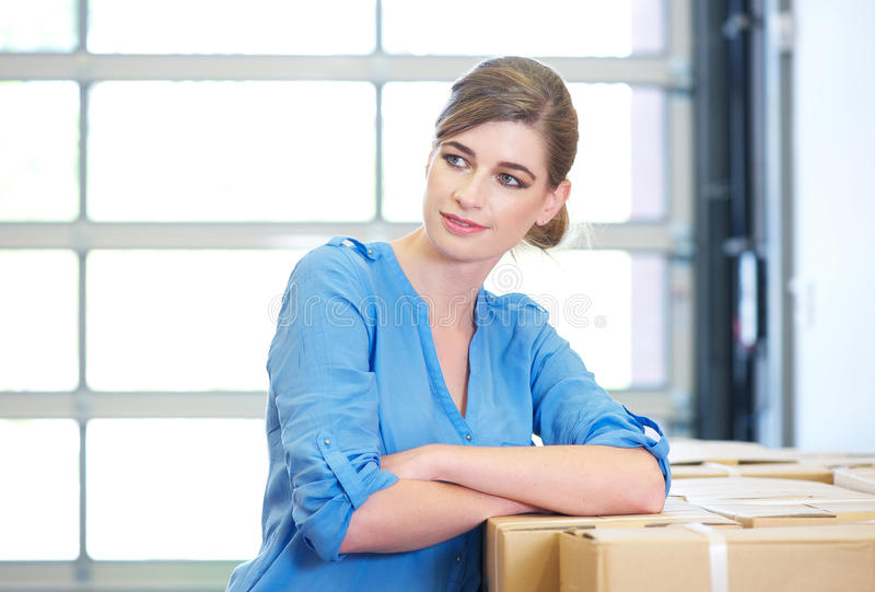Download Portrait Of A Businesswoman Relaxing Next To Boxes In Warehouse Stock Image - Image: 31500059