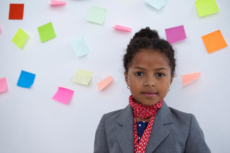 Portrait of businesswoman standing against sticky notes on wall royalty free stock photo