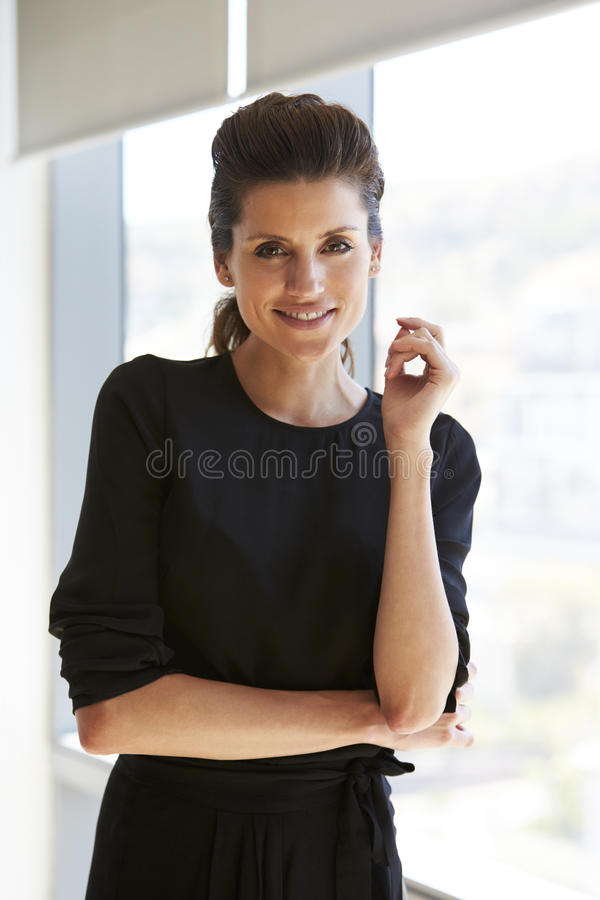 Portrait Of Businesswoman Standing By Window In Office stock photography