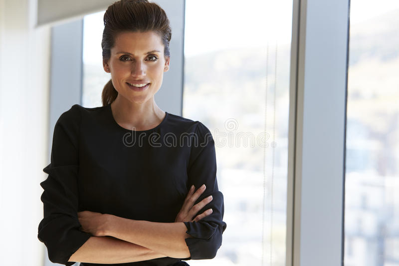 Portrait Of Businesswoman Standing By Window In Office stock image