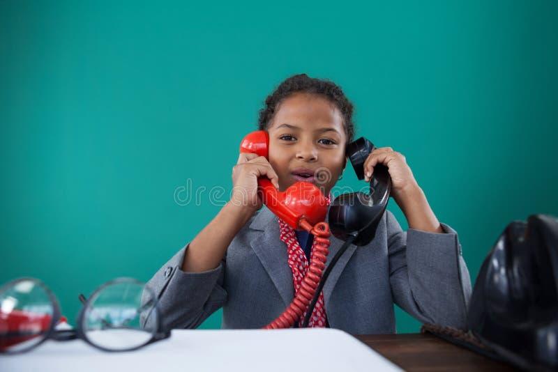 Portrait of businesswoman talking land line phones at desk royalty free stock image