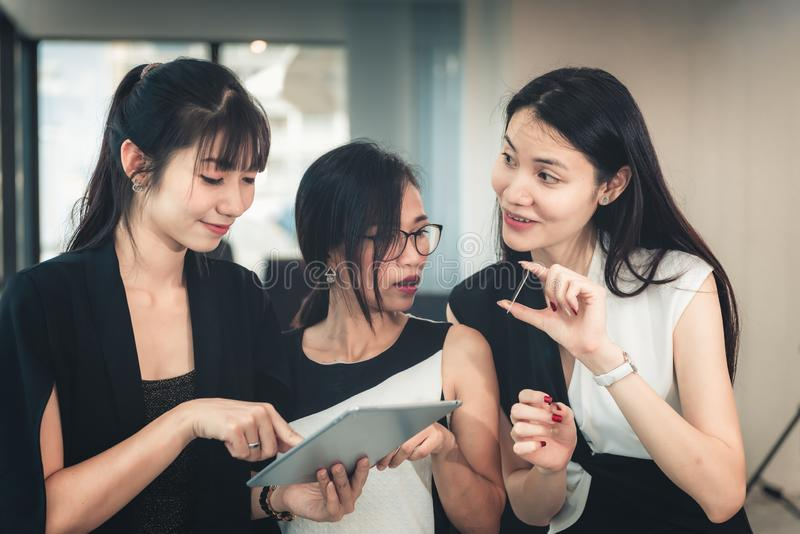 Portrait of Businesswomen Enjoying Shopping Online in Office Workplace, Asian Women Discussing Something About Credit Card While. Shopping Online With Tablet royalty free stock photo