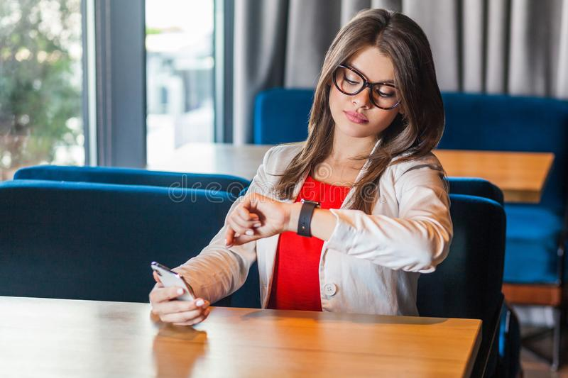 Portrait of busy beautiful stylish brunette young woman in glasses sitting and checking time on her smart watch with serious face stock image
