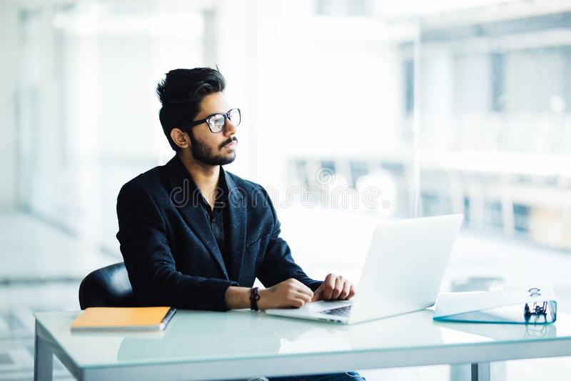 Portrait of a busy indian guy multitasking, taking notes, reading paper, surfing internet with laptop in office stock photo