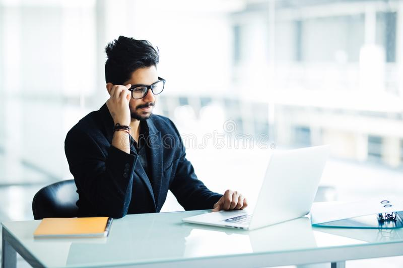 Portrait of a busy indian guy multitasking, taking notes, reading paper, surfing internet with laptop in office royalty free stock photos