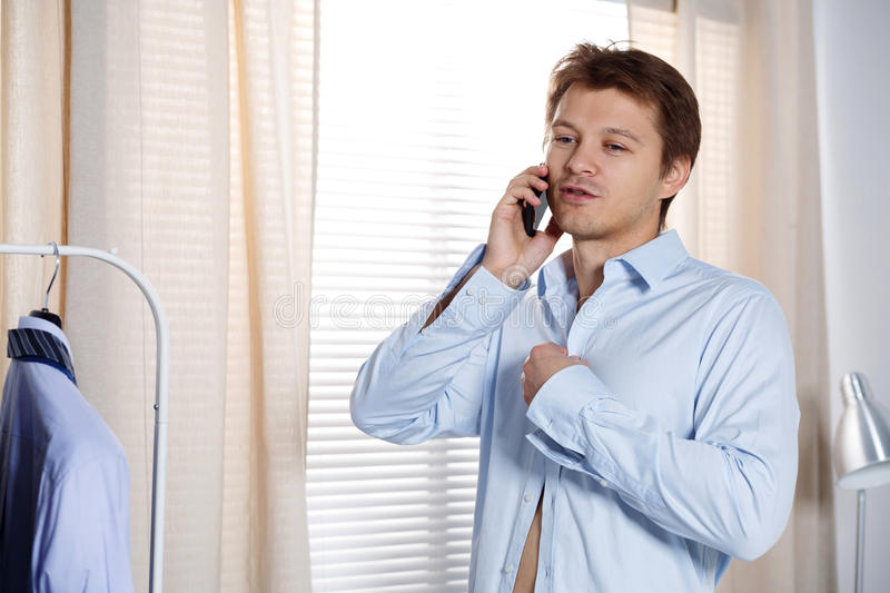 Portrait of busy young man putting on his shirt and talking on p stock photography