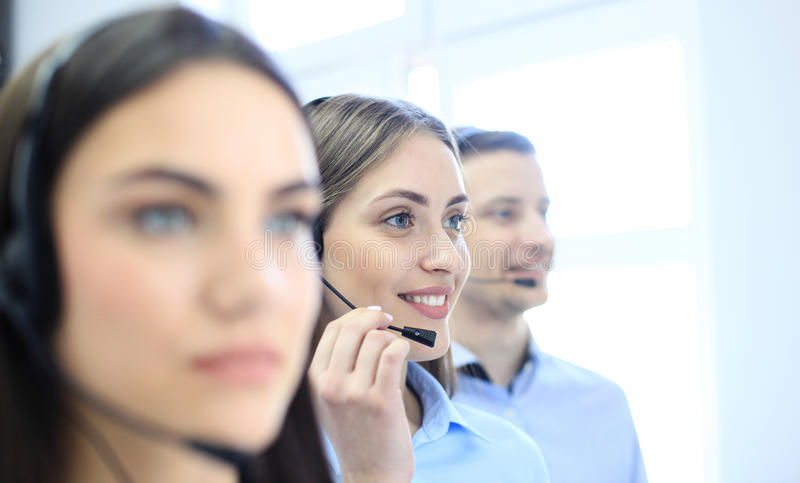 Portrait of call center worker accompanied by her team. Smiling customer support operator at work. stock images