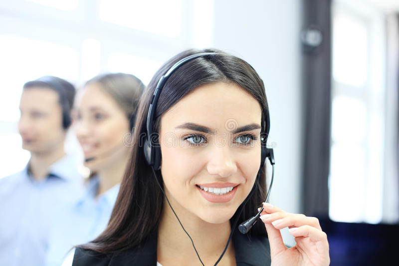 Portrait of call center worker accompanied by her team. Smiling customer support operator at work. royalty free stock photography