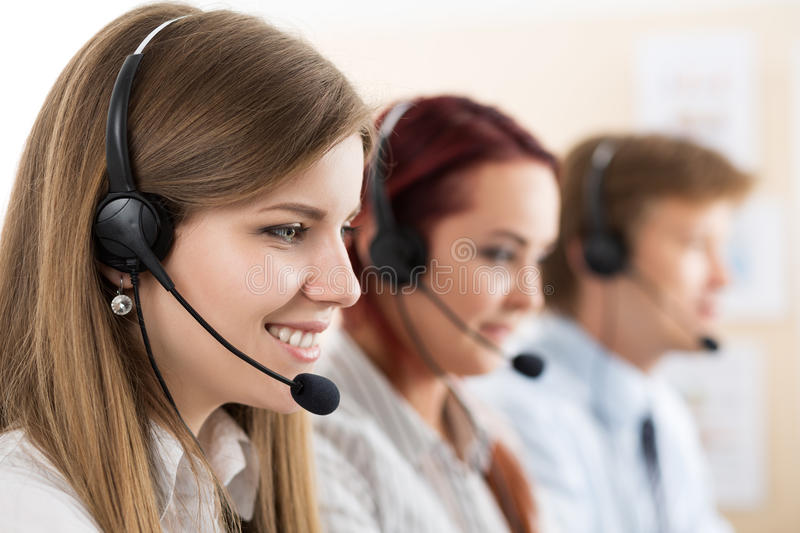 Portrait of call center worker accompanied by her team stock image