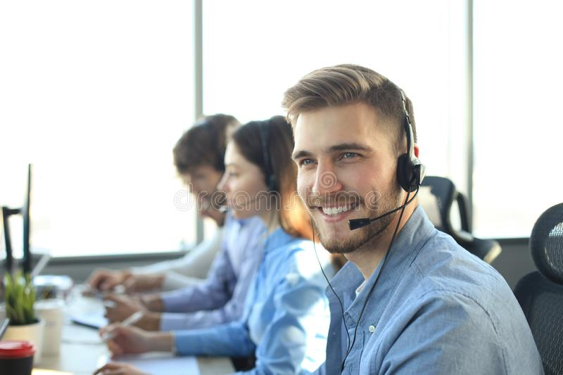 Portrait of call center worker accompanied by his team. Smiling customer support operator at work. stock photo