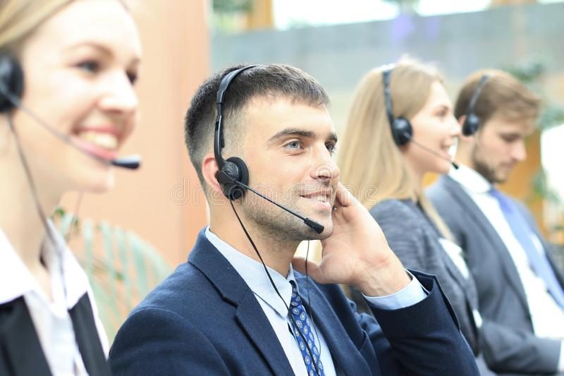 Portrait of call center worker accompanied by his team. Smiling customer support operator at work. stock images