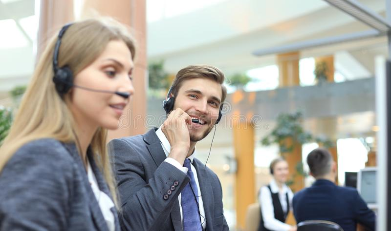 Portrait of call center worker accompanied by his team. Smiling customer support operator at work royalty free stock images