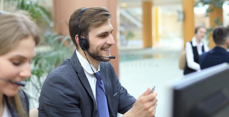 Portrait of call center worker accompanied by his team. Smiling customer support operator at work royalty free stock photo