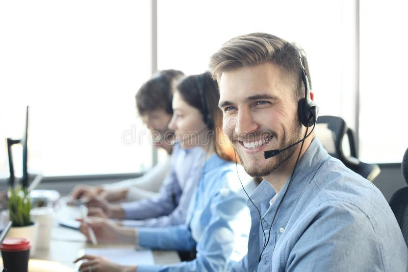Portrait of call center worker accompanied by his team. Smiling customer support operator at work. royalty free stock image