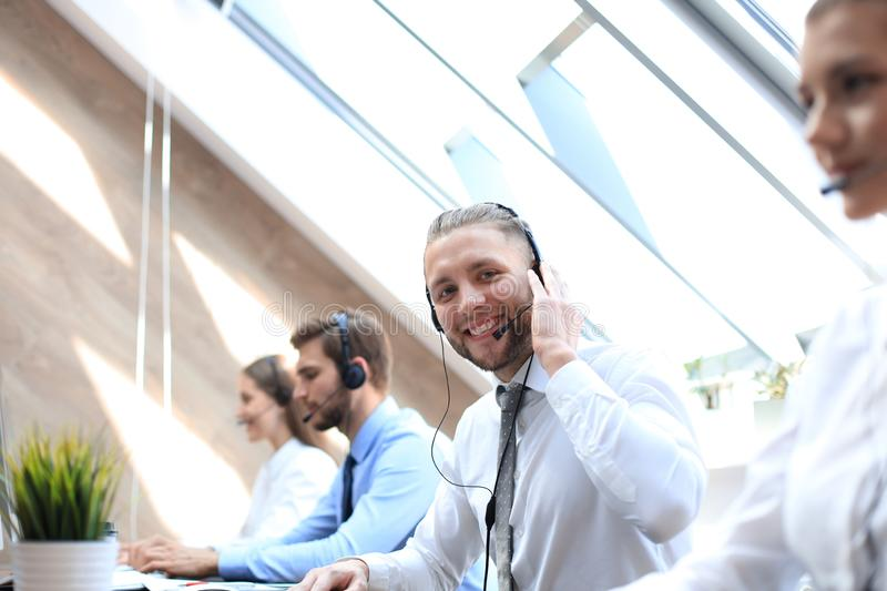 Portrait of call center worker accompanied by his team. Smiling customer support operator at work stock photography