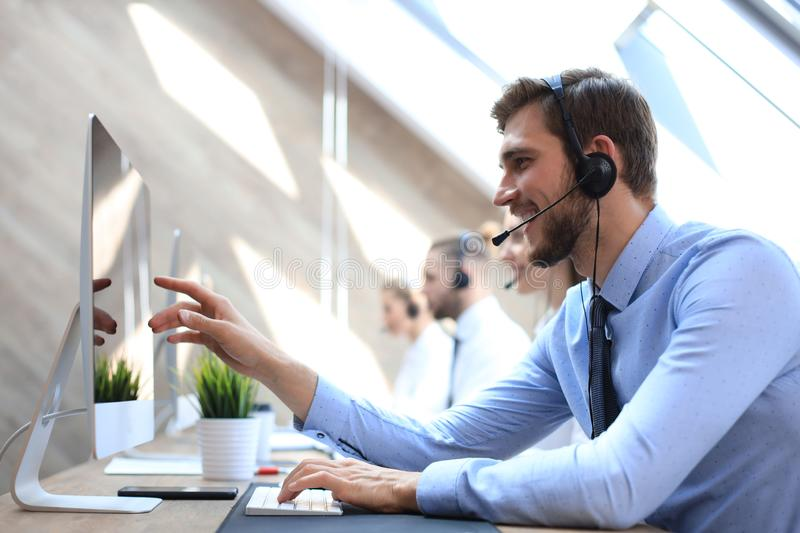 Portrait of call center worker accompanied by his team. Smiling customer support operator at work stock images