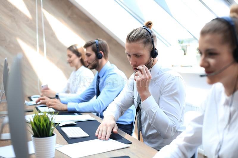 Portrait of call center worker accompanied by his team. Smiling customer support operator at work royalty free stock photography