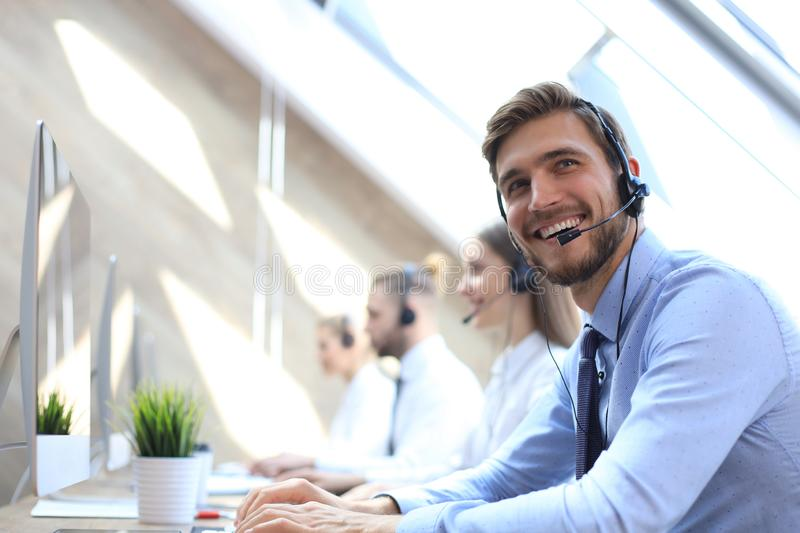 Portrait of call center worker accompanied by his team. Smiling customer support operator at work stock image