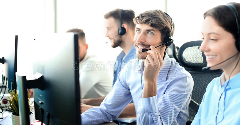 Portrait of call center worker accompanied by his team. Smiling customer support operator at work. royalty free stock photo