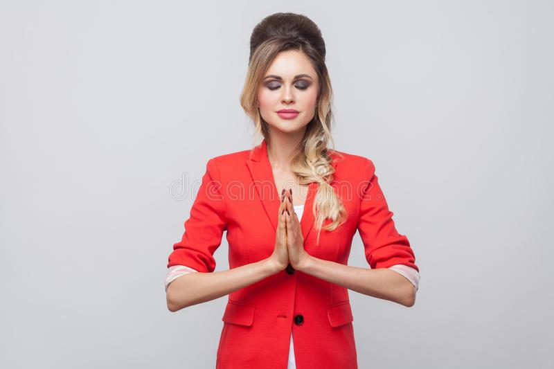 Portrait of calm beautiful business lady with hairstyle and makeup in red fancy blazer, standing with closed eyes and palm hands. Gesture yoga pose. indoor stock photos