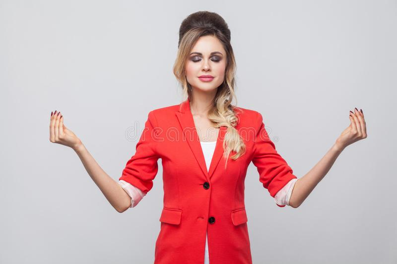 Portrait of calm beautiful business lady with hairstyle and makeup in red fancy blazer, standing with closed eyes and raised arms. Yoga pose gesture. indoor royalty free stock images