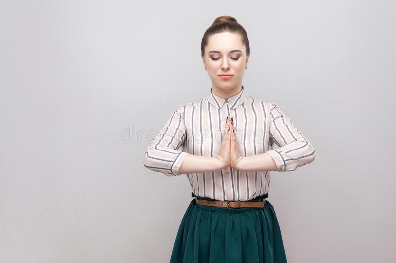 Portrait calm of beautiful young woman in striped shirt, green skirt with makeup and collected ban hairstyle, standing with closed stock photography