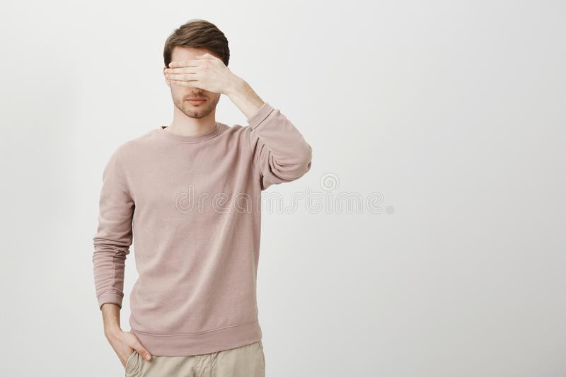 Portrait of calm caucasian male with bristle holding hand in pocket while covering eyes and standing against gray. Background. Guy do not like when girlfriend royalty free stock images