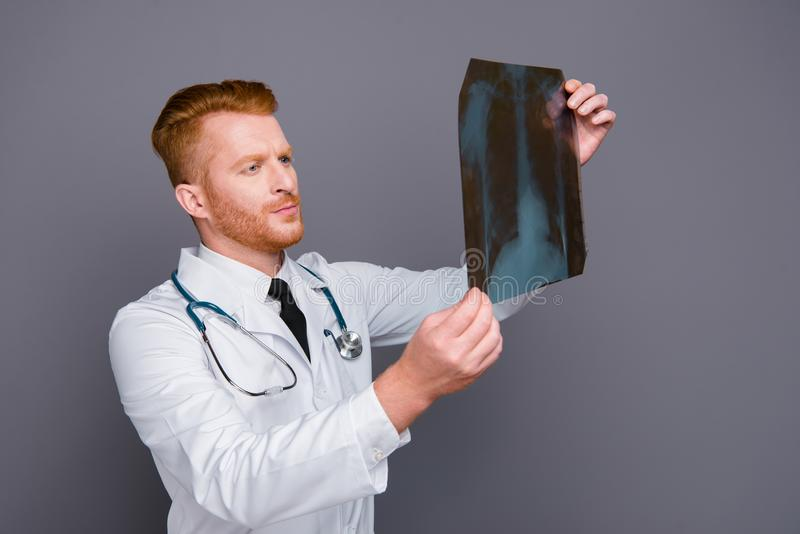 Portrait of calm doctor looking problem on image isolated on dar. K gray background stand in white wear stock photos