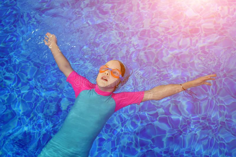 Portrait of calm girl relaxing in clear blue water of outdoors sunny swimming pool. royalty free stock image