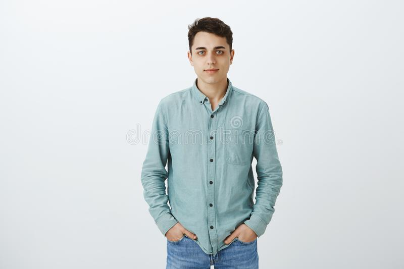 Portrait of calm good-looking male university student in casual shirt, holding hands in pockets and smiling at camera stock photos