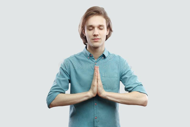 Portrait of calm handsome long haired blonde young man in blue casual shirt standing in yoga pose and meditating, and try to relax royalty free stock photo