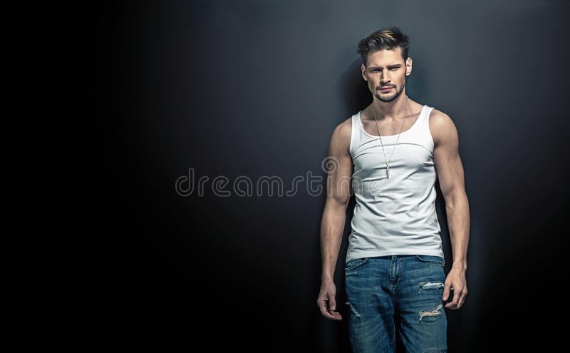Portrait of a calm, handsome young man posing on a black background royalty free stock photos
