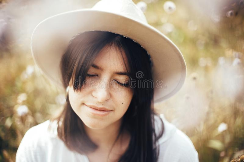 Portrait of calm hipster girl in hat relaxing in wildflower meadow,  traveling in sunny mountains. Stylish carefree woman enjoying royalty free stock photos