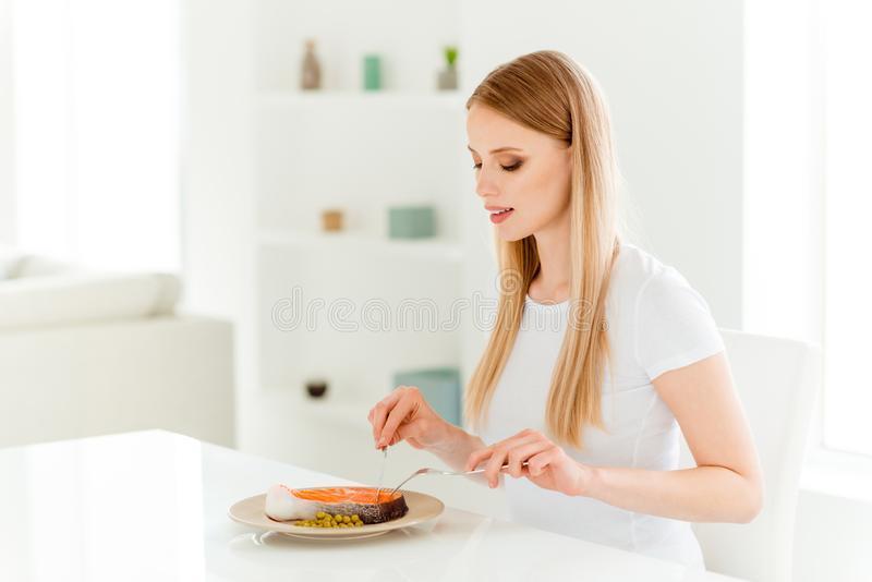 Portrait of calm positive millennial youth enjoy have dinner snack use fork knife eat delicious dish with proteins stock photos