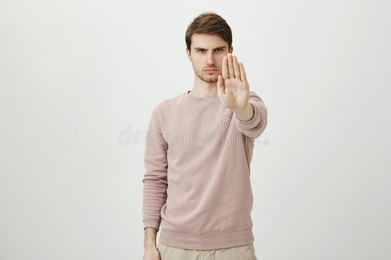Portrait of calm serious young man with bristle stretching hand towards camera with stop or hold gesture, standing royalty free stock image