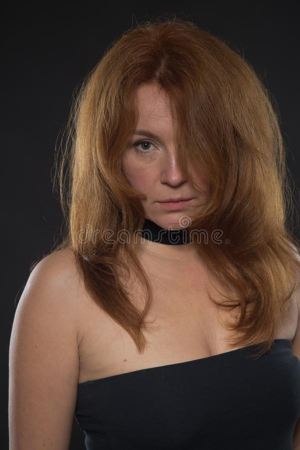 Portrait of calm woman in bare shoulder black dress royalty free stock image