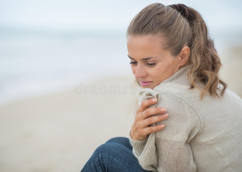 Portrait of calm woman sitting on cold beach royalty free stock photo