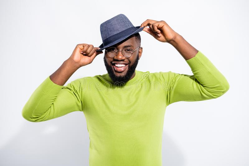 Portrait of candid person guy touching his cap laughing wearing green jumper  over white background. Portrait of candid person guy touching his cap laughing royalty free stock images