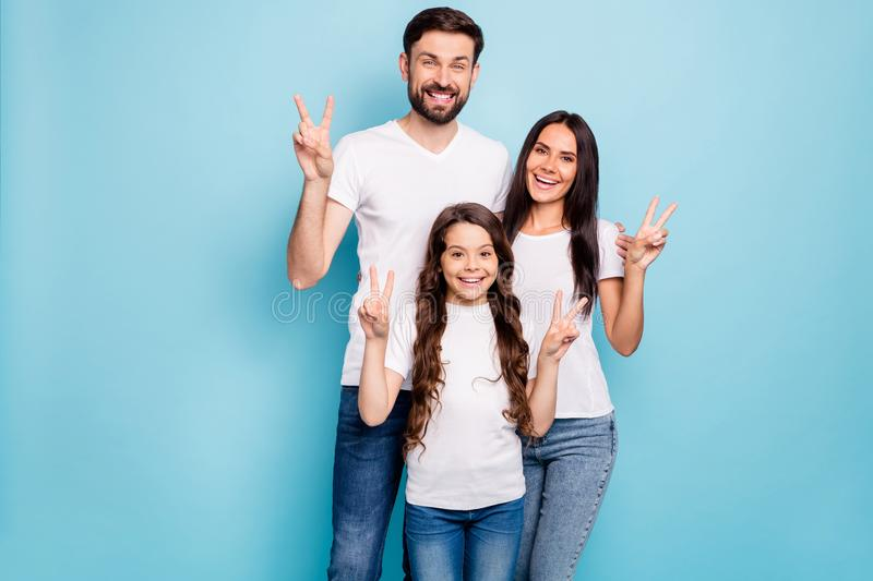 Portrait of candid three people promoters hug embrace have brunet hair make v-signs wear white t-shirt denim jeans royalty free stock photography