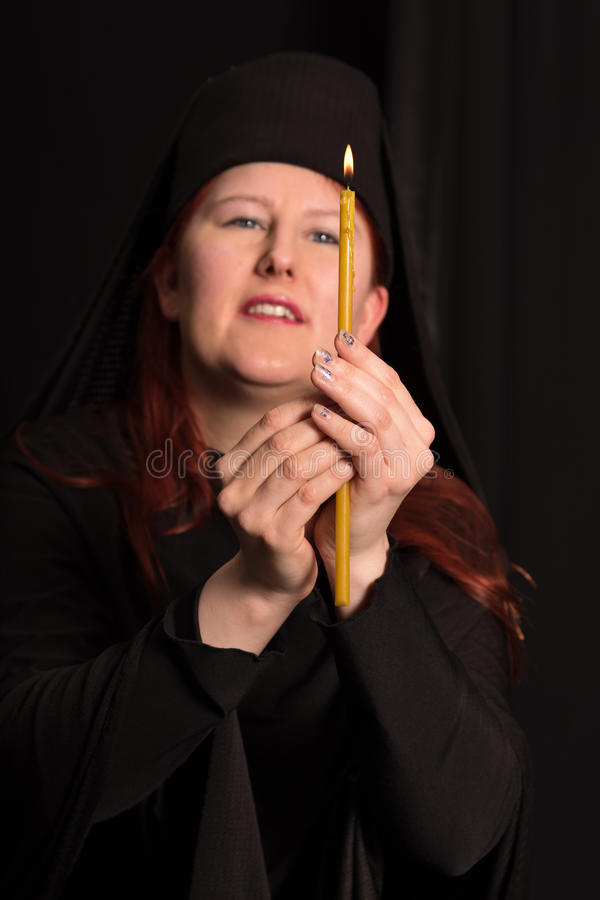 Portrait with candle . Woman in black and candle on black background stock images