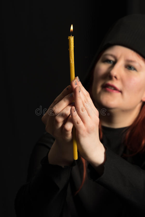 Portrait with candle . Woman in black and candle on black background royalty free stock image