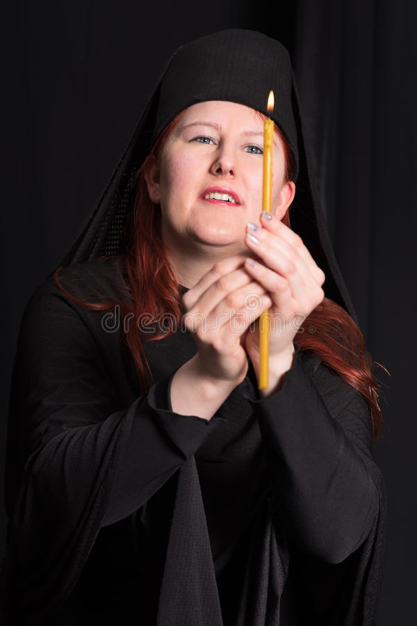 Portrait with candle . Woman in black and candle on black background royalty free stock images