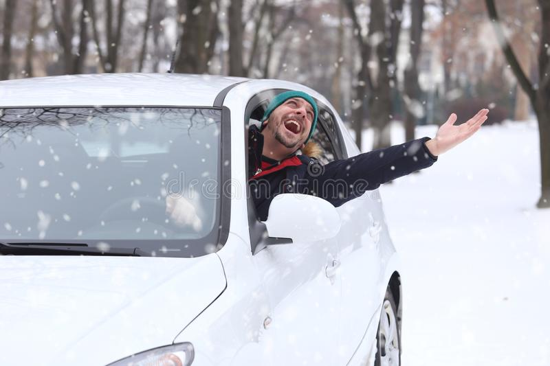 Portrait of car driver with santa hat through car window enjoying the snowy day. On the road winter vacation and holidays concept. royalty free stock photography