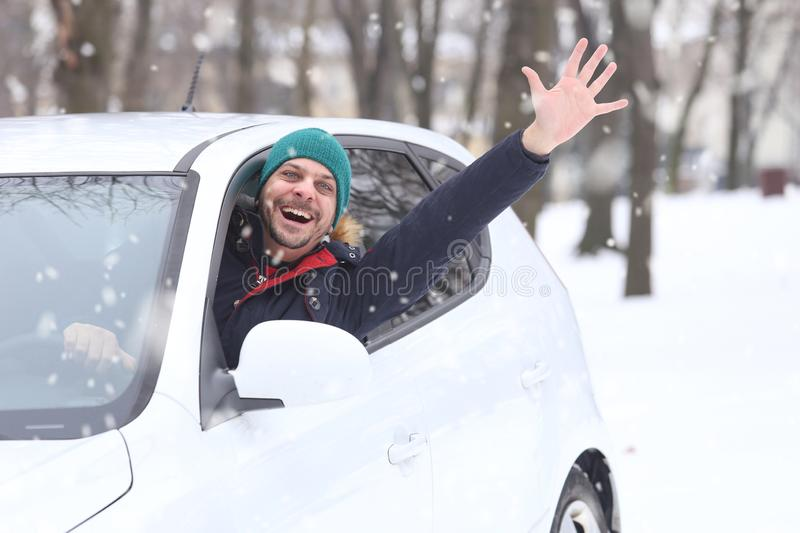 Portrait of car driver with santa hat through car window enjoying the snowy day. On the road winter royalty free stock image