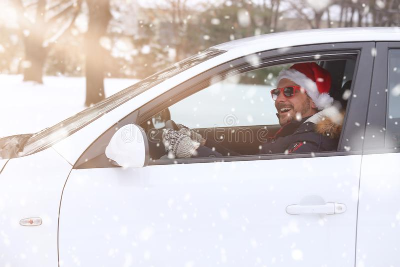 Portrait of car driver with santa hat enjoying the snow and sunny dan. royalty free stock images