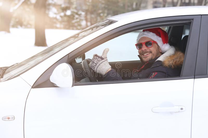 Portrait of car driver with santa hat and thumb up enjoying the stock image