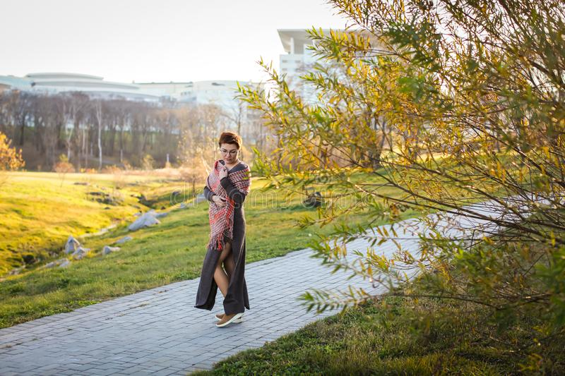 Portrait of carefree caucasian woman with short haircut in warm casual clothes at autumn park in selective focus stock photo